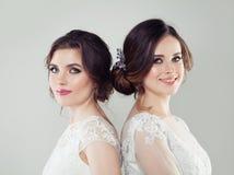 Jeune mariée de deux belle femmes avec le maquillage et la coiffure nuptiale photographie stock libre de droits