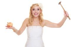 Jeune mariée de femme avec le marteau environ pour heurter la tirelire Photographie stock