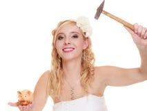 Jeune mariée de femme avec le marteau environ pour heurter la tirelire Images stock