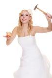 Jeune mariée de femme avec le marteau environ pour heurter la tirelire Photos stock