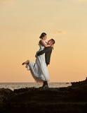 Jeune mariée de levage de marié sur le coucher du soleil orange Images stock