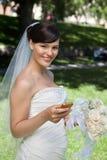 Jeune mariée de nouveaux mariés tenant le téléphone portable Images stock