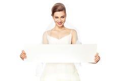 Jeune mariée de sourire avec la publicité. Photos libres de droits