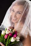 Jeune mariée de sourire avec un bouquet des tulipes avec un voile Images libres de droits