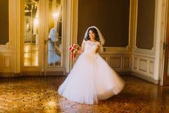 Jeune mariée de sourire dans la robe de mariage luxueuse tenant un bouquet mignon posant sur le fond de l'intérieur en bois de vi Image libre de droits