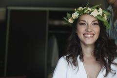 Jeune mariée de sourire heureuse avec une guirlande sur sa tête Photographie stock libre de droits