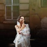 Jeune mariée de sourire heureuse magnifique de brune en position blanche de robe de vintage Photographie stock libre de droits