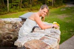 Jeune mariée de sourire se penchant sur le mur en pierre Photo libre de droits