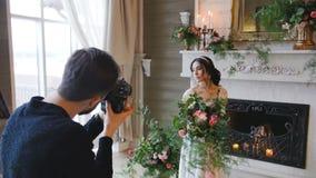 Jeune mariée de tir de photographe avec un bouquet et une cheminée sur le fond banque de vidéos