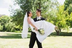 Jeune mariée de transport de marié dans des bras au jardin Image stock