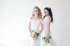 Jeune mariée deux l'épousant avec un bouquet des fleurs épousant des cheveux photo stock