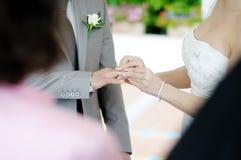Jeune mariée donnant l'anneau de mariage à son marié Photographie stock