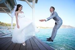 Jeune mariée donnant un coup de pied un jeune marié, épousant pré les couples thaïlandais de photographie Image libre de droits