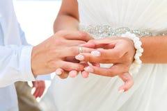 Jeune mariée donnant une bague de fiançailles à son marié sous le deco de voûte Photos libres de droits
