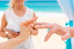 Jeune mariée donnant une bague de fiançailles à son marié sous le deco de voûte Photographie stock
