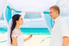 Jeune mariée donnant une bague de fiançailles à son marié sous le deco de voûte Images stock