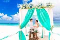 Jeune mariée donnant une bague de fiançailles à son marié sous le deco de voûte Photos stock
