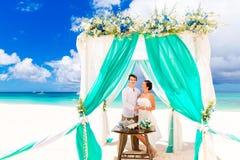 Jeune mariée donnant une bague de fiançailles à son marié sous le deco de voûte Photo libre de droits