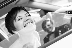 Jeune mariée drôle dans le marié de sourire de voiture Femme 35 ans mariage Photographie stock