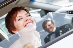 Jeune mariée drôle rousse dans le marié de sourire de voiture Femme 35 ans mariage Image libre de droits