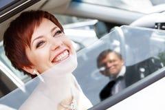 Jeune mariée drôle rousse dans le marié de sourire de voiture Femme 35 ans mariage Images libres de droits