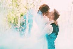 Jeune mariée embrassant le marié dans la fumée de turquoise sur la nature Images libres de droits