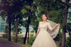Jeune mariée en parc avec un voile de dentelle avec l'espace de copie Images stock