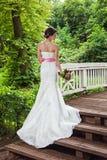 Jeune mariée en parc sur le pont Photo stock