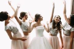 Jeune mariée et amis dans la chambre d'hôtel légère Photo stock
