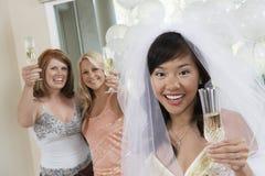 Jeune mariée et amis tenant Champagne Flute Photographie stock libre de droits