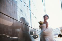 Jeune mariée et bouquet sur des bâtiments de miroir de backround Image stock