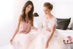 Jeune mariée et demoiselle d'honneur de sourire s'asseyant sur le lit Image stock