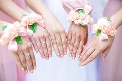 Jeune mariée et demoiselles d'honneur avec des bracelets de fleur sur des mains closeup Image stock