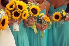 Jeune mariée et demoiselles d'honneur avec le bouquet de tournesols Photographie stock libre de droits