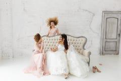 Jeune mariée et demoiselles d'honneur dupant autour et champagne de boissons Image stock