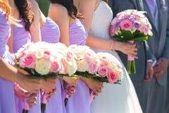 Jeune mariée et demoiselles d'honneur tenant des bouquets images stock