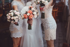 Jeune mariée et demoiselles d'honneur tenant des bouquets Photographie stock libre de droits