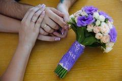 Jeune mariée et groom& x27 ; mains de s avec des anneaux de mariage sur la table brune Photographie stock libre de droits