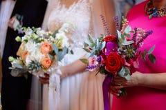 Jeune mariée et marraine tenant des bouquets de mariage pendant la cérémonie de mariage photo libre de droits