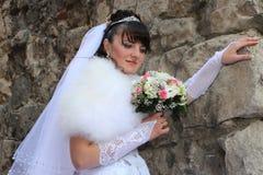 jeune mariée et mur en pierre Photos libres de droits