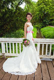 Jeune mariée féerique avec du charme en parc sur le pont Photo stock