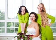 Jeune mariée gaie avec la demoiselle d'honneur tenant le bouquet Image libre de droits
