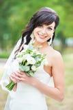 Jeune mariée gaie avec le bouquet de fleur fraîche dehors Photographie stock libre de droits