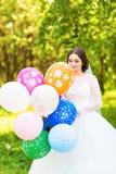 Jeune mariée gaie avec le groupe de ballons Image libre de droits