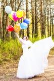 Jeune mariée gaie avec le groupe de ballons extérieurs Photo stock