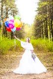 Jeune mariée gaie avec le groupe de ballons extérieurs Images stock