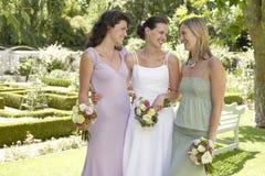 Jeune mariée gaie et amis tenant des bouquets dans le jardin Photographie stock libre de droits