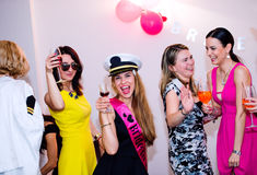 Jeune mariée gaie et demoiselles d'honneur célébrant la partie de poule avec des boissons Photos stock