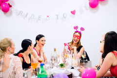Jeune mariée gaie et demoiselles d'honneur célébrant la partie de poule avec des boissons Photographie stock
