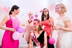 Jeune mariée gaie et demoiselles d'honneur célébrant la partie de poule avec des boissons Photo libre de droits